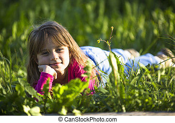 Little funny girl lying in the green grass.