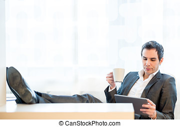 Businessman with his feet on the desk enjoying a cup of...