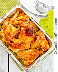 Chicken wings fried with vegetables in pan from foil