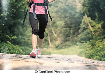 young woman hiker walking on trail