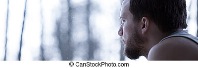 Depressed young man looking through the window