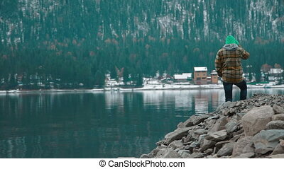 Man stands on the shore of the lake