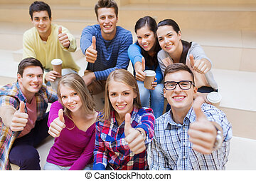 group of smiling students with paper coffee cups -...