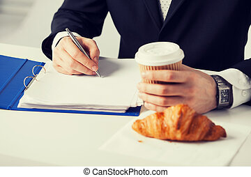 businessman with coffee writing something - businessman on...