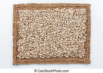 Frame of burlap and sunflower seeds, lying on a white...