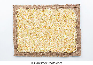 Frame of burlap and millet grain, lying on a white...