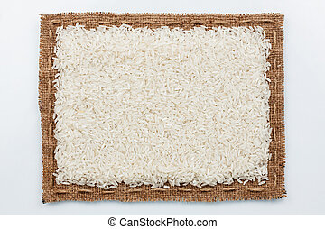 Frame of burlap and rice grain, lying on a white background