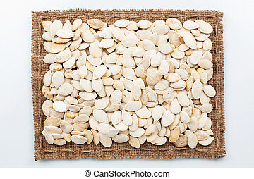 Frame of burlap and pumpkin seeds, lying on a white...