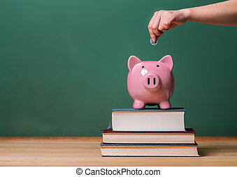 Person depositing money in a piggy bank on top of books with...