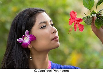 Pretty Vietnamese girl with a flower in her hair taking a...