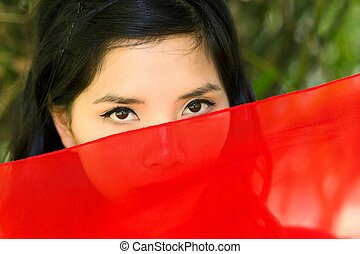 vietnamese woman peeking over red fabric at the camera so...