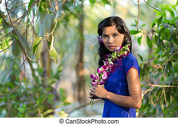 Pretty Woman in Blue Dress Holding Purple Flower - Close up...