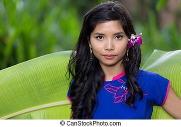 Pretty serious young Vietnamese woman with a fresh orchid...