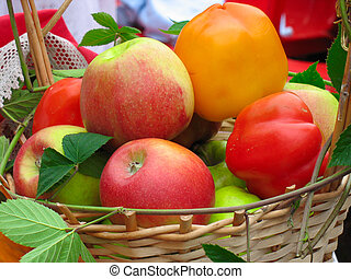 Harvesting apples, leaves and sweet peppers in wooden basket...