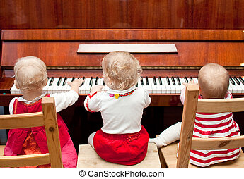 Piano lesson - Three little baby girls playing a piano