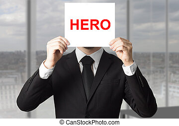 businessman hiding face behind sign hero - businessman in...
