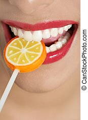 Colorful Lollypop in perfect woman teeth and red lips mouth