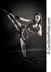 Beautiful girl kicking with the leg black and white