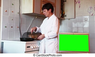 Woman prepares food in the kitchen.