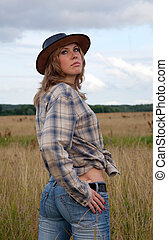 cowgirl in jeans and a cowboy hat at nature - portrait of...