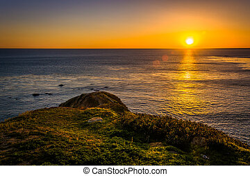 Sunset over a grassy hill and the Pacific Ocean, seen from...