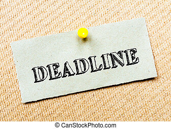 Recycled paper note pinned on cork board. Deadline message....