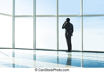 Business - Silhouette back view of young businessman is...