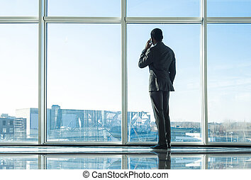 Business - Back view of young businessman is looking out of...