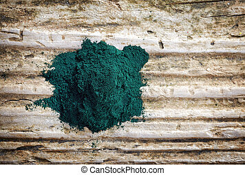 heap of spirulina algae powder on wooden background, top...