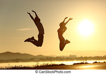 Fitness couple jumping happy at sunset with the sun in the...