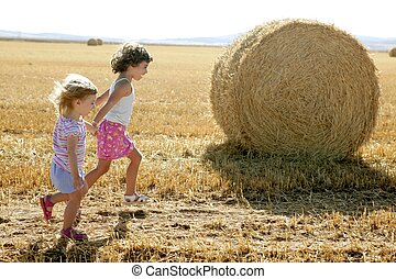 Girls playing with the round wheat dried bales outdoor...