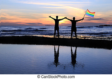 Gay men holding a pride flag. - Silhouette of a gay couple...