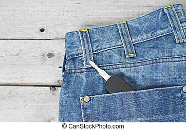 Car key in blue jeans back pocket against wooden background
