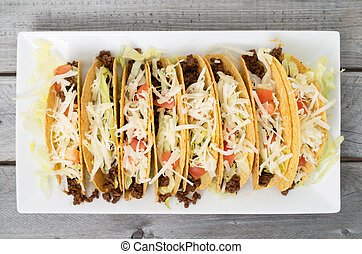 Ground beef tacos with cheese lettuce and tomatoes against...