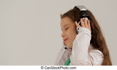 Portrait of Little Girl In Headphones Listening to Music And Dancing. Slow motion