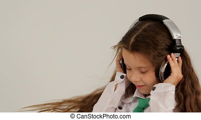 Portrait of Little Girl In Headphones Listening to Music And...