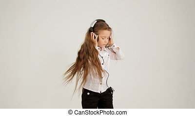 Little Girl Listening to Music With Headphones And Dancing. Video shot in opposite direction.