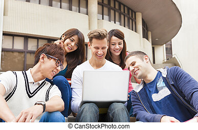 Happy  young group of students watching the laptop