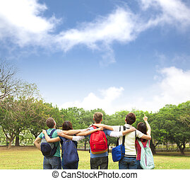 Happy young group of students watching the sky