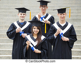 young students in graduation gowns on university campus