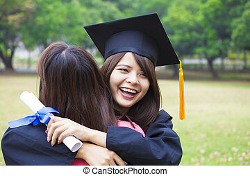 young female graduate hugging her friend at graduation...