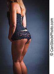 woman in lingerie, back, ass on a gray background - woman in...