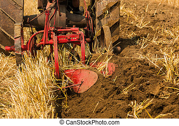 Red Plough - On vintage red plough turning over the soil.
