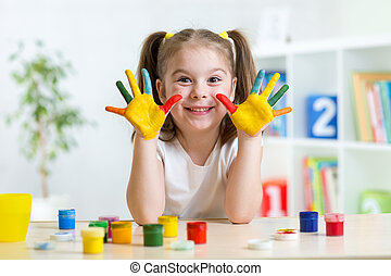 cute kid girl with hands painted in colorful paints in...