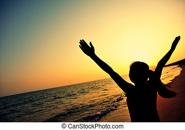 cheering young woman open arms to sunset at sea