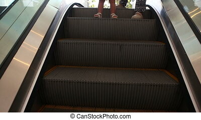 small child and her mother move on escalator