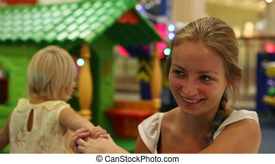 child pulls mother to toy house - little blonde child pulls...
