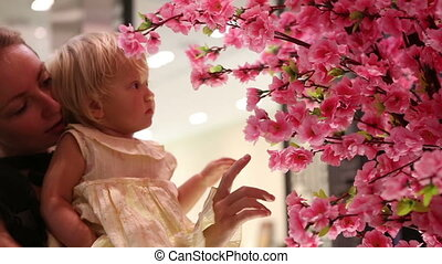 child touches sakura flowers sitting on mother arms - blonde...