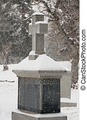 tombstone2 - snow covered tombstone with cross in cemetary