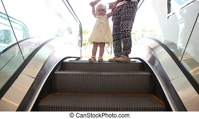small child and her mother move on escalator - small blonde...